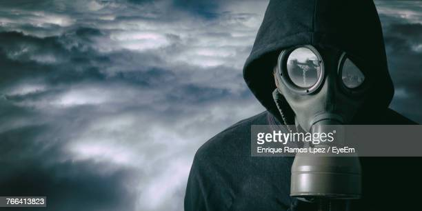 close-up of man wearing glass against cloudy sky - gas mask stock pictures, royalty-free photos & images