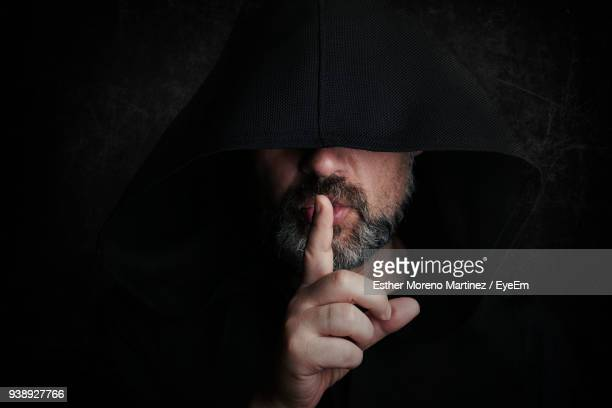 close-up of man wearing halloween costume with finger on lips by wall - finger on lips stock pictures, royalty-free photos & images