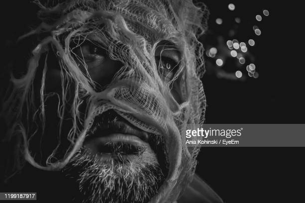 close-up of man wearing mask against black background - black mask disguise stock pictures, royalty-free photos & images