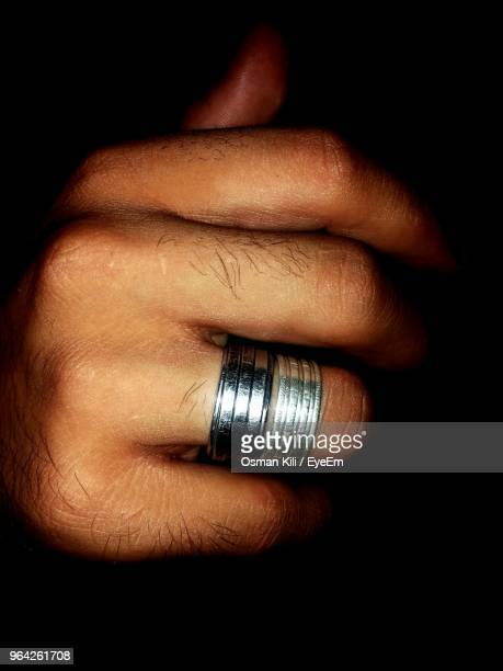 Close-Up Of Man Wearing Ring Against Black Background