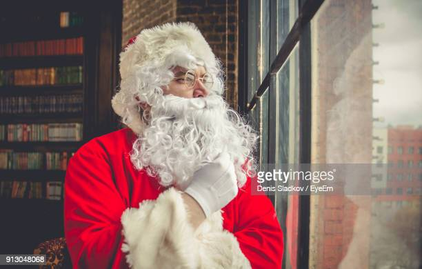 close-up of man wearing santa claus costume by window at home - santa close up stock pictures, royalty-free photos & images