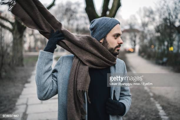 close-up of man wearing scarf at park during winter - schal stock-fotos und bilder
