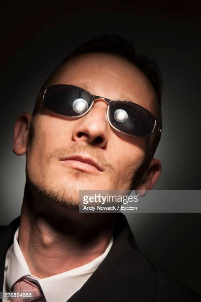 Close-Up Of Man Wearing Sunglasses Against Black Background