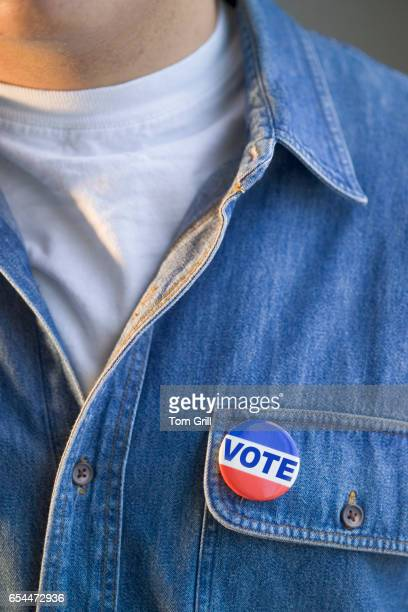 "closeup of man wearing ""vote"" pin - pin stock pictures, royalty-free photos & images"