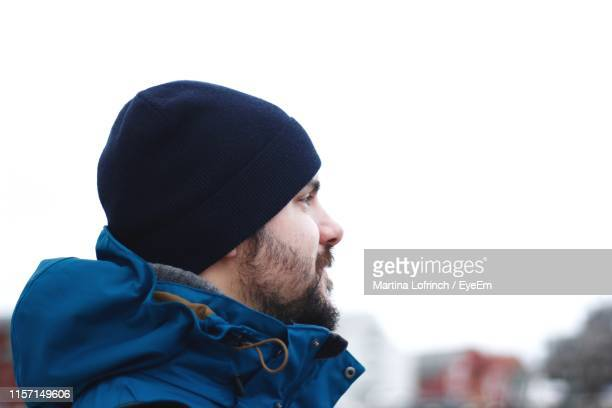 close-up of man with cap against clear sky - knit hat stock pictures, royalty-free photos & images