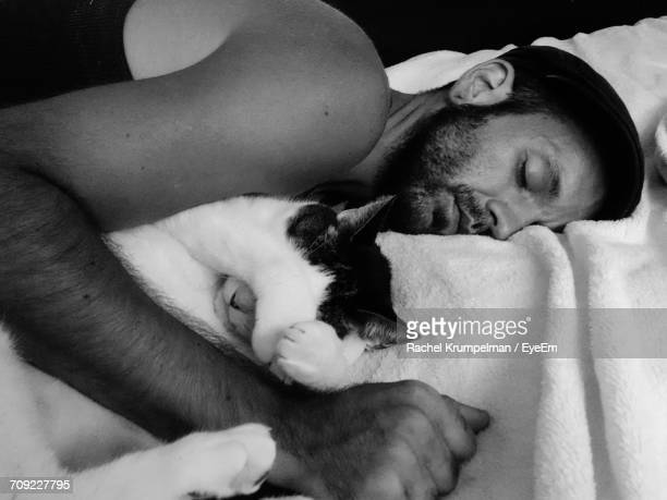 Close-Up Of Man With Cat Sleeping On Bed At Home