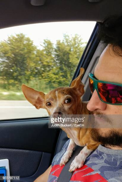 Close-Up Of Man With Dog In Car