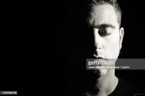 close-up of man with eyes closed against black background - eyes closed stock pictures, royalty-free photos & images
