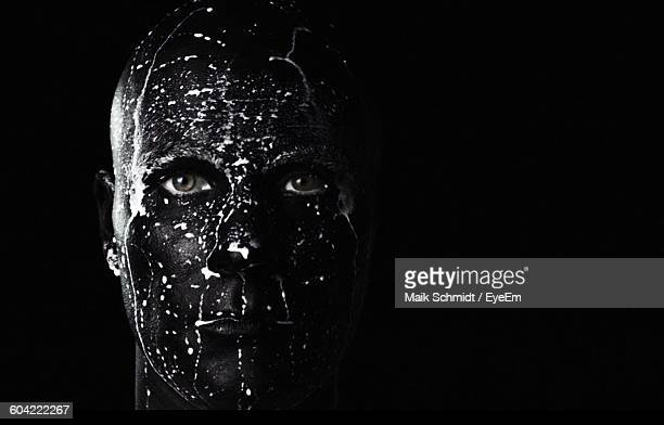 close-up of man with face paint against black background - body paint stock-fotos und bilder