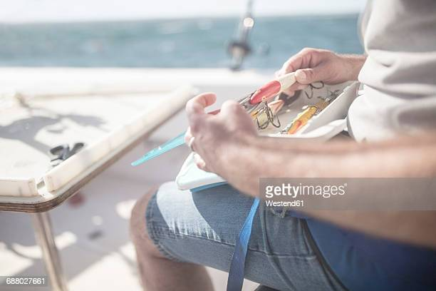Close-up of man with fishing equipment on boat