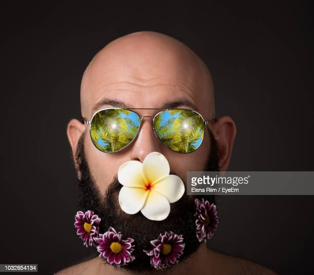 close-up of man with flowers in mouth and beard against black background - elena blume stock-fotos und bilder