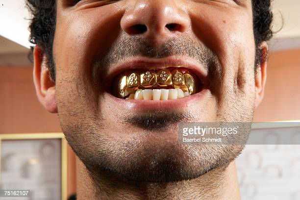 close-up of man with gold teeth - gold tooth stock photos and pictures