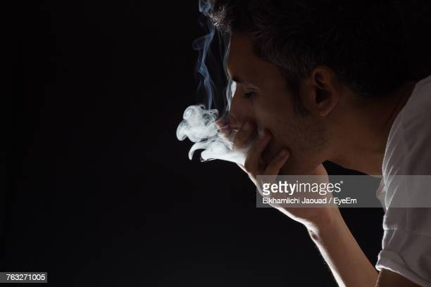 Close-Up Of Man With Hand Covering Mouth Emitting Smoke Against Black Background