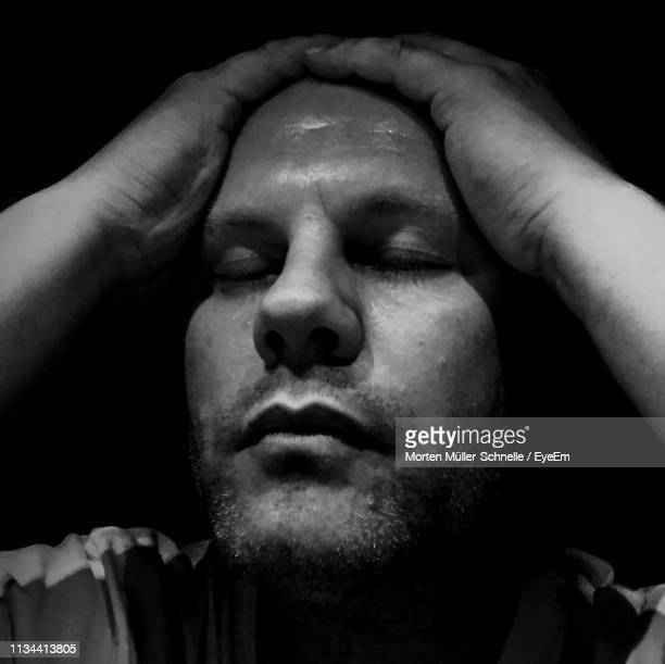 Close-Up Of Man With Headache Against Black Background