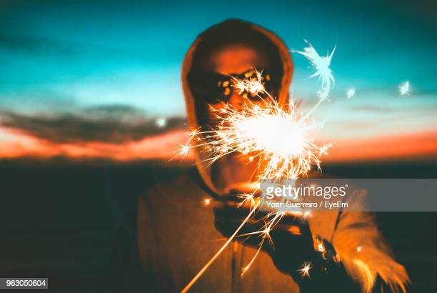 close-up of man with lit sparkler during sunset - 25 29歳 ストックフォトと画像