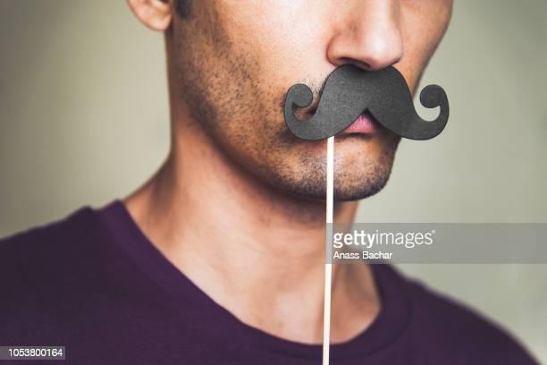 close-up of man with mustache prop - stoppelbart stock-fotos und bilder