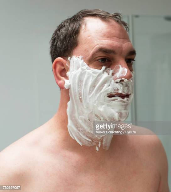 Close-Up Of Man With Shaving Cream On Face In Bathroom