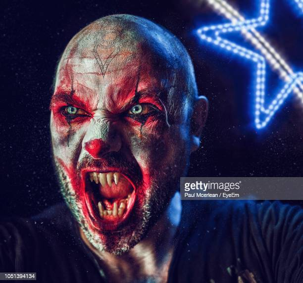 close-up of man with spooky make-up screaming in darkroom - scary clown makeup stock photos and pictures