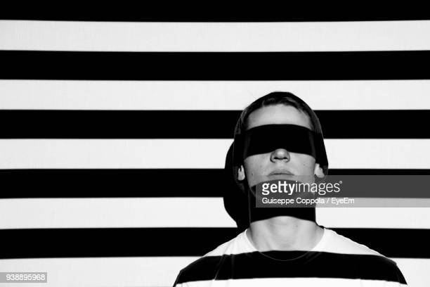 Close-Up Of Man With Striped Shadow Against Wall