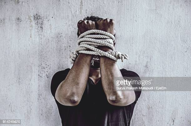 Close-Up Of Man With Tied Hands Against Wall