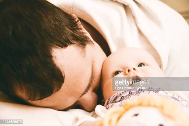 close-up of man with toddler daughter lying on bed - liga cerina stock pictures, royalty-free photos & images