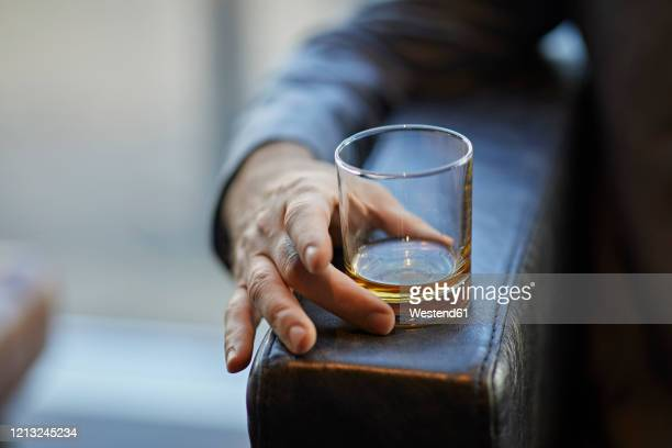 close-up of man with whiskey glass on arm rest of a leather chair - alcohol stock pictures, royalty-free photos & images