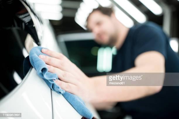 close-up of man working in modern car factory wiping finished car - acabando - fotografias e filmes do acervo