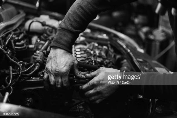 Close-Up Of Man Working On Motorcycle