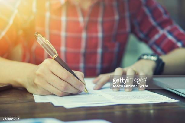 close-up of man working on table - signing stock pictures, royalty-free photos & images