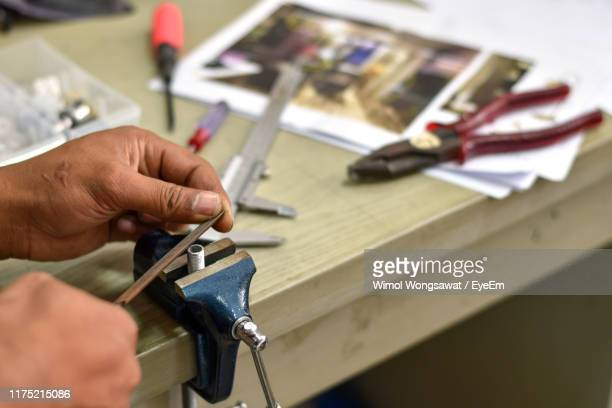 close-up of man working on workbench at workshop - wimol wongsawat stock photos and pictures