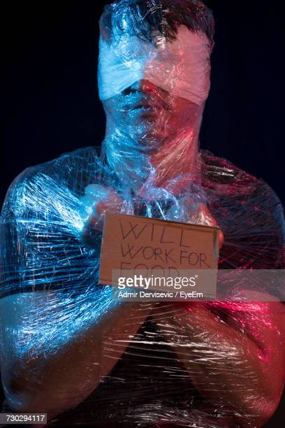 close-up of man wrapped in plastic with \will work for food\ sign - man wrapped in plastic stock pictures, royalty-free photos & images