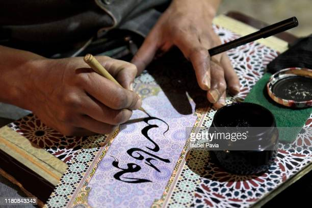 close-up of man writing arabic calligraphy - arabic style stock pictures, royalty-free photos & images