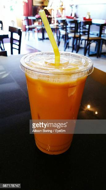 Close-Up Of Mango Lassi In Disposable Cup On Table