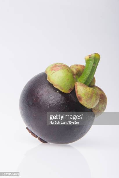 close-up of mangosteen against white background - mangosteen stock photos and pictures