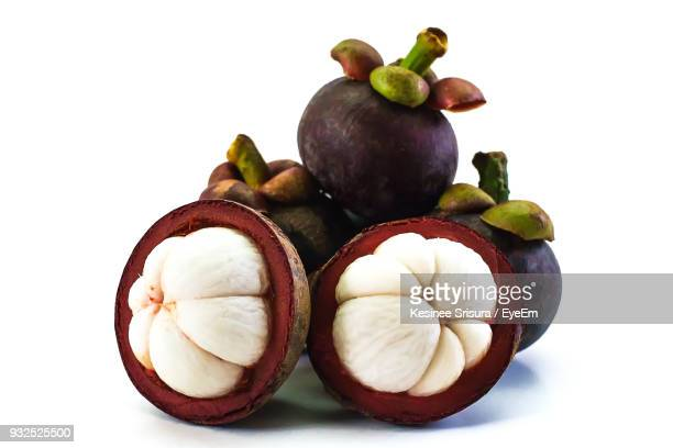 close-up of mangosteens against white background - mangosteen stock photos and pictures