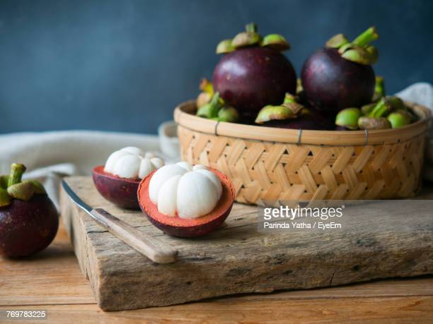 close-up of mangosteens in basket on table - mangosteen stock photos and pictures