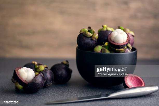 close-up of mangosteens in bowl on table - mangosteen stock photos and pictures