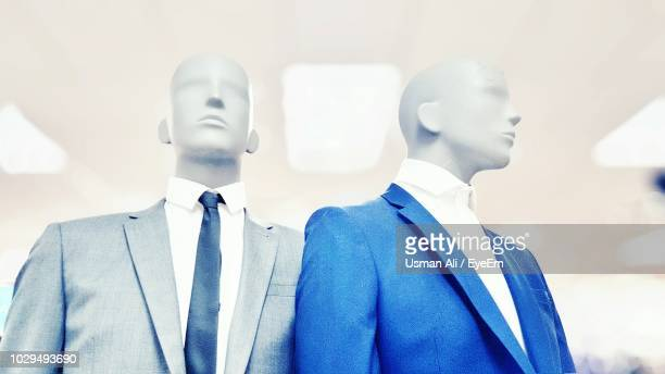 close-up of mannequins wearing suits for sale in clothing store - male likeness stock pictures, royalty-free photos & images