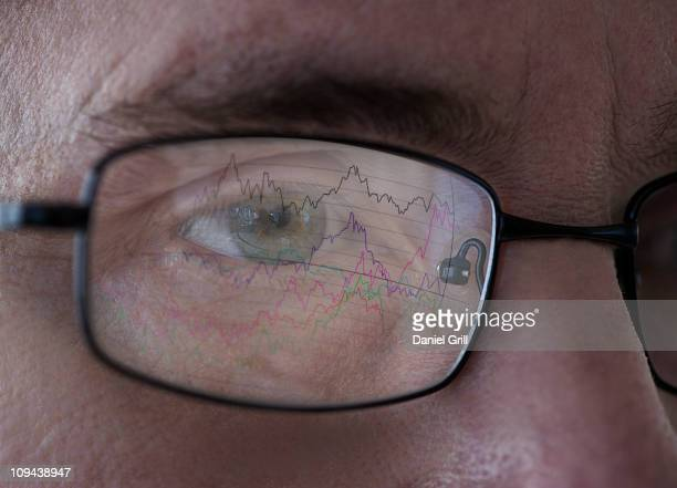 Close-up of man's eye with graph reflecting in glasses