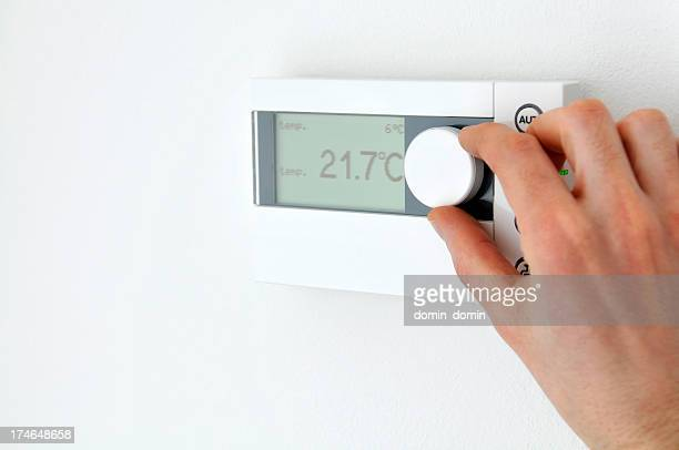 close-up of man's hand adjusting an electronic thermostat, home interior - thermostat stock photos and pictures