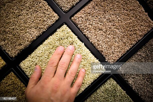Close-up of man's hand feeling carpet samples