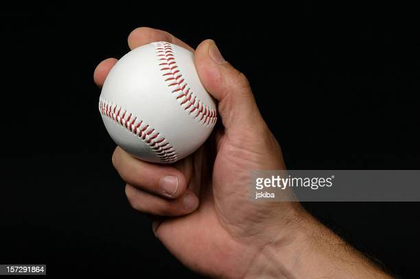 close-up of man's hand griping a baseball - baseball trajectory stock photos and pictures