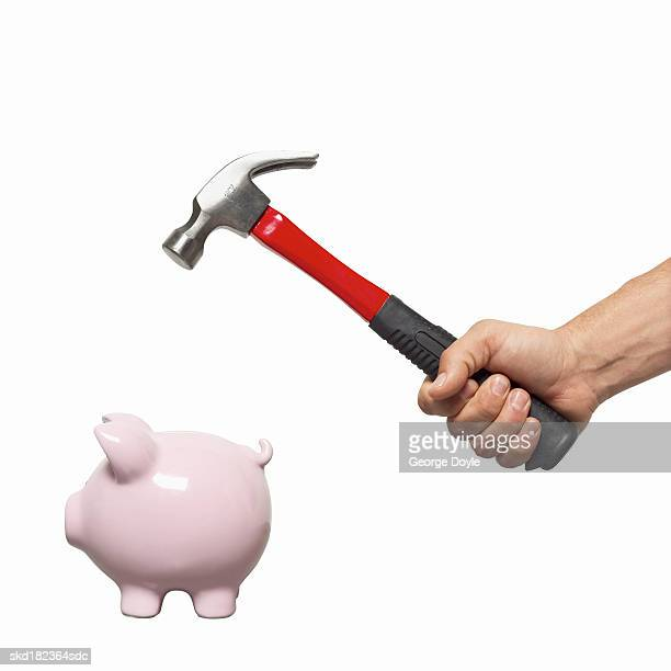 Close-up of man's hand holding hammer about to strike piggy bank