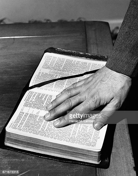 close-up of mans hand on bible - number of people stock pictures, royalty-free photos & images