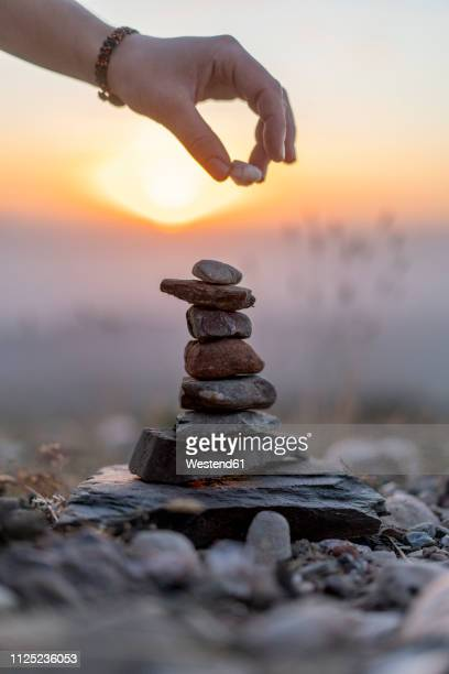 Close-up of man's hand placing stone on cairn at sunset