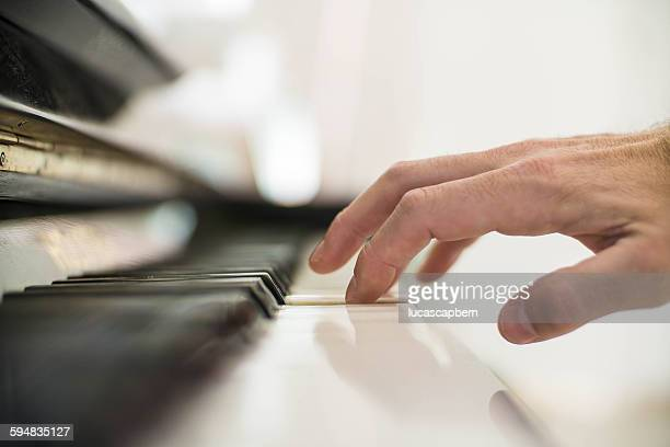 Close-up of man's hand playing the piano