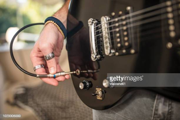 close-up of man's hand plugging electric guitar - electric guitar stock pictures, royalty-free photos & images