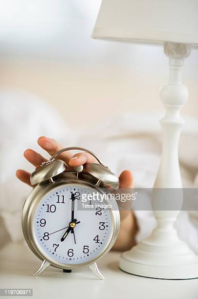 Close-up of man's hand reaching to alarm clock from bed