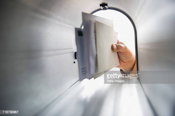 close-up of man's hand removing letters from letter box - mail stock pictures, royalty-free photos & images