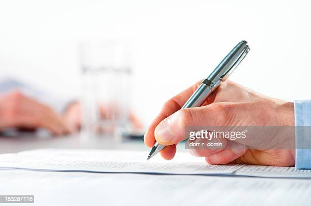 Close-up of man's hand signing document on desk, office interior